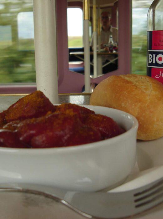 Currywurst mit einem Brötchen und Kaltgetränk im Bordbistro der Deutschen Bahn in einem Zug