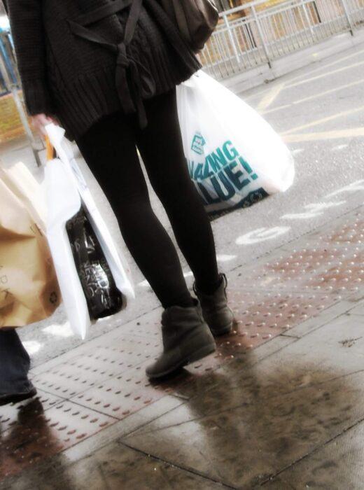Zwei Frauen mit Einkaufstüten an einer Straße, unter anderem sind die Taschen von der Modekette Primark