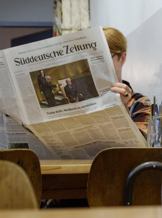 Eine Frau sitzt im Cafe und liest gemütlich eine gedruckte Ausgabe der Süddeutschen Zeitung