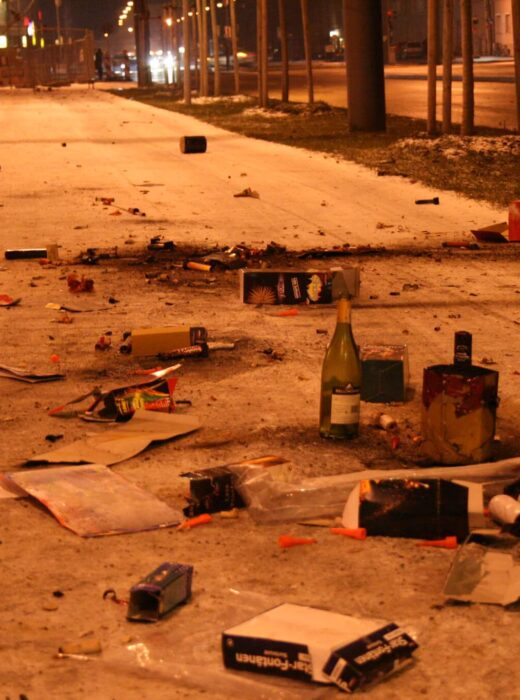 Bürgersteig voll mit Flaschen, abgebrannten Feuerwerkskörpern und sonstigem Müll in der Silvesternacht